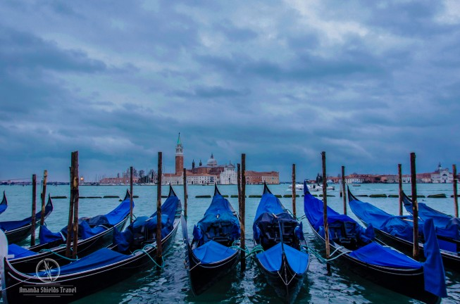 Several blue gondolas on blue water against a blue sky